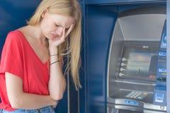 Femme triste se tenant devant une machine de banque d'atmosphère argent d'isolement aucuns jeunes de femme blanc photos stock