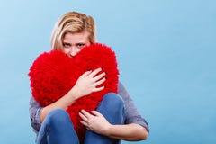 Femme triste tenant l'oreiller rouge dans la forme de coeur Image stock