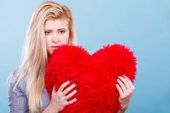 Femme triste tenant l'oreiller rouge dans la forme de coeur Photographie stock