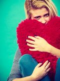 Femme triste tenant l'oreiller rouge dans la forme de coeur Photos libres de droits