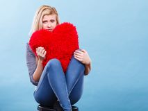 Femme triste tenant l'oreiller rouge dans la forme de coeur Photos stock