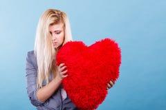 Femme triste tenant l'oreiller rouge dans la forme de coeur Photo libre de droits