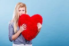 Femme triste tenant l'oreiller rouge dans la forme de coeur Image libre de droits