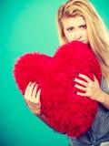 Femme triste tenant l'oreiller rouge dans la forme de coeur Photo stock