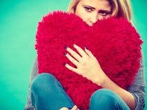 Femme triste tenant l'oreiller rouge dans la forme de coeur Images stock