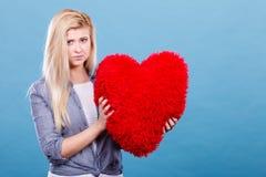 Femme triste tenant l'oreiller rouge dans la forme de coeur Images libres de droits