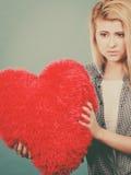 Femme triste tenant l'oreiller rouge dans la forme de coeur Photographie stock libre de droits