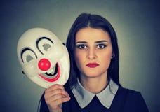 Femme triste tenant le masque de clown exprimant le bonheur de gaieté photo stock
