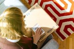 Femme unboxing déballant Amazone COM enferment dans une boîte Photos stock