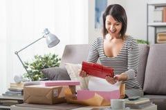 Femme unboxing un colis images stock