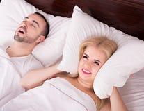 Femme Unsleeping et homme de ronflement Photos stock