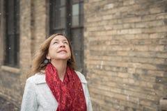 Femme urbaine regardant la chute de neige Images stock