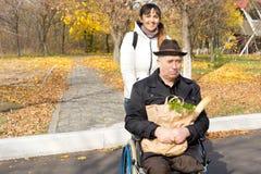 Femme utile poussant un homme supérieur dans un fauteuil roulant Photos libres de droits