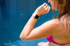 Femme utilisant la montre numérique en main par la piscine photographie stock libre de droits