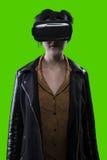 Femme utilisant le casque de VR sur un fond d'écran vert image libre de droits
