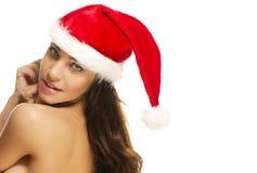 Femme utilisant le chapeau de Santa regardant au-dessus de son épaule Photo libre de droits