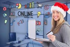 Femme utilisant le chapeau de Santa tout en faisant des emplettes en ligne Photos stock