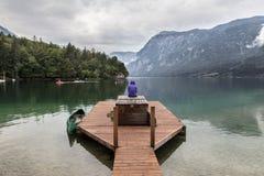 Femme utilisant le hoodie pourpre observant la scène obscurcie tranquille de matin au lac Bohinj, montagnes d'Alpes, Slovénie Photographie stock libre de droits