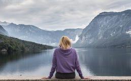 Femme utilisant le hoodie pourpre observant la scène obscurcie tranquille de matin au lac Bohinj, montagnes d'Alpes, Slovénie Photo stock