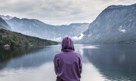 Femme utilisant le hoodie pourpre observant la scène obscurcie tranquille de matin au lac Bohinj, montagnes d'Alpes, Slovénie Photographie stock