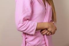 Femme utilisant le peignoir rose Photo stock