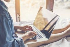 Femme utilisant le réseau social de travail d'ordinateur portable faisant des emplettes en ligne à la maison photos stock