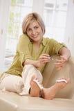 Femme utilisant le vernis à ongles Image libre de droits