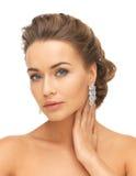 Femme utilisant les boucles d'oreille brillantes de diamant Photos stock