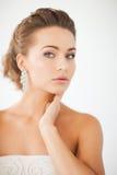 Femme utilisant les boucles d'oreille brillantes de diamant Photographie stock libre de droits