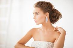 Femme utilisant les boucles d'oreille brillantes de diamant Photo libre de droits