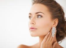 Femme utilisant les boucles d'oreille brillantes de diamant Photos libres de droits