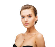 Femme utilisant les boucles d'oreille brillantes de diamant Photographie stock