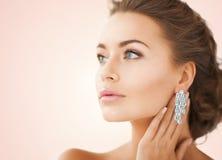 Femme utilisant les boucles d'oreille brillantes de diamant Images libres de droits