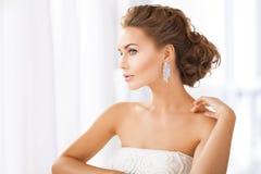 Femme utilisant les boucles d'oreille brillantes de diamant Images stock