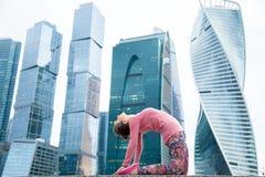 Femme utilisant les vêtements de sport roses dans la pose de chameau Image libre de droits