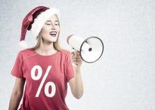 Femme utilisant un chapeau de Santa Claus et utilisant un T-shirt rouge tenant un mégaphone Photographie stock