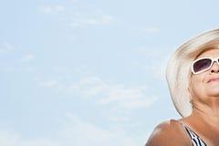 Femme utilisant un chapeau de soleil et des lunettes de soleil Photographie stock libre de droits