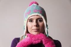 Femme utilisant un chapeau tricoté tenant ses mains sous son menton Photographie stock libre de droits