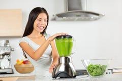 Femme végétale de smoothie mélangeant les smoothies verts Images stock