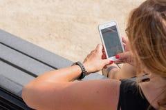 Femme vérifiant des buts de forme physique sur le smartphone images stock