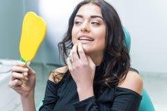 Femme vérifiant des dents dans le miroir images libres de droits
