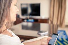 Femme vérifiant des messages à son téléphone portable Image stock