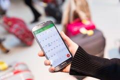 Femme vérifiant l'information de calendrier au téléphone portable se reposant dans le terminal d'aéroport Photo libre de droits