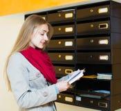 Femme vérifiant la correspondance au lobby photographie stock