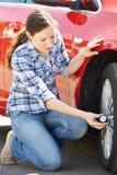 Femme vérifiant la pression de pneu de voiture utilisant la mesure Photo libre de droits