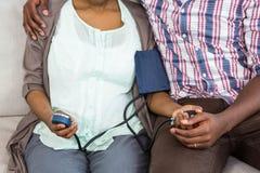 Femme vérifiant la tension artérielle tout en se reposant avec l'homme dans le salon Photo libre de droits