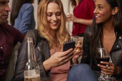 Femme vérifiant le téléphone portable à la partie avec des amis Image libre de droits