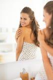 Femme vérifiant le teint dans la salle de bains Image libre de droits