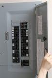 Femme vérifiant les fusibles automatiques au panneau de commande électrique Photographie stock libre de droits