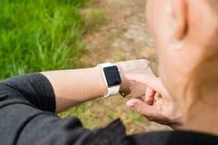 Femme vérifiant sa montre d'Apple tout en marchant Images libres de droits